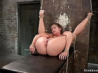 Gagged brown-haired babe in rope bondage gets her dress cutted and then in extraordinary rope bondage gets firm flogged