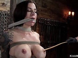 Gagged by rope and tied to wooden post big tits brunette slave is flogged then master canes her