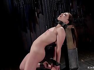 Brunette in rubber lingerie in device bondage