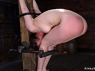 Black-haired slave locked head and wrists in iron device gets punched by her tough sir