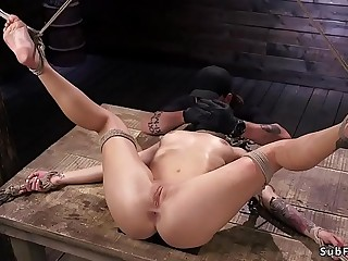Suspended slave gagged with black dildo